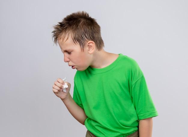 Chory chłopiec w zielonej koszulce czuje się niedobrze, kaszle i stoi nad białą ścianą