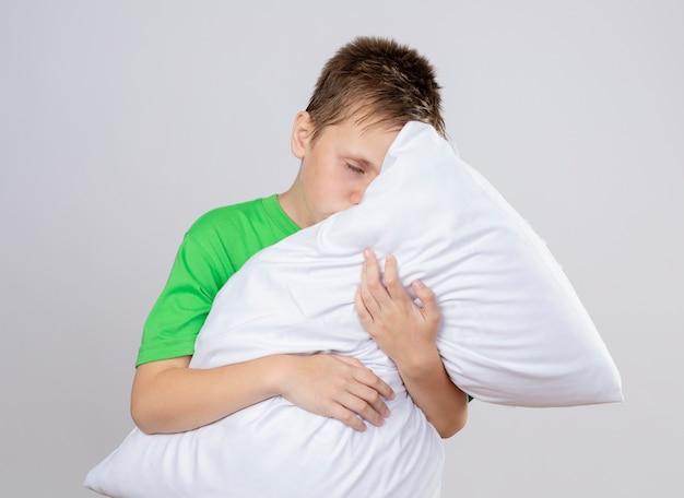 Chory chłopiec w zielonej koszulce źle się czuje przytulając poduszkę z zamkniętymi oczami stojąc na białej ścianie