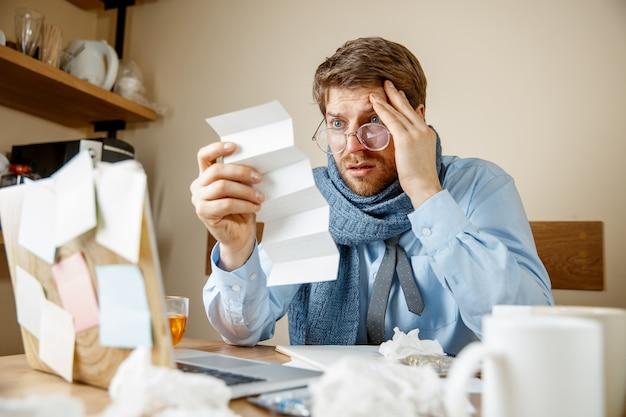 Chory człowiek czytający lekarstwa na receptę pracuje w biurze, biznesmen przeziębiony, grypa sezonowa. pandemia grypy, zapobieganie chorobom, choroby, wirusy, infekcje, temperatura, gorączka i koncepcja grypy