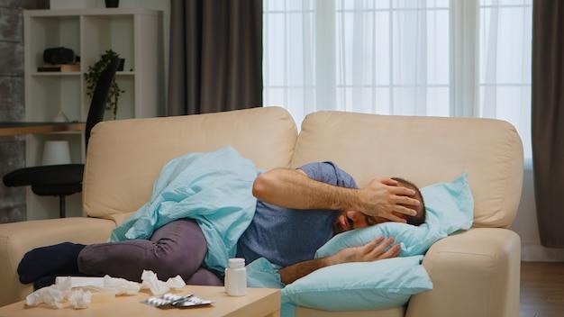 Chory człowiek leżący na kanapie, sprawdzając swoje pigułki podczas izolacji chrząstki.