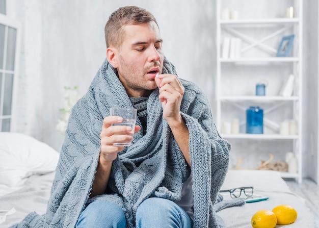 Chory człowiek owinięty w szalik siedzi na łóżku biorąc pigułki z wodą