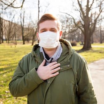 Chory człowiek ubrany w maskę medyczną w miejskim parku publicznym