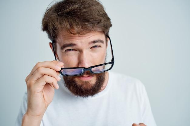 Chory człowiek w okularach w ręku problemy ze wzrokiem jasnym tle. zdjęcie wysokiej jakości