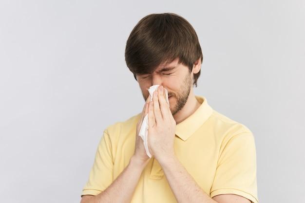 Chory człowiek z objawami grypy kichanie nosem w białą tkankę na białym tle na szarej ścianie, kopia przestrzeń