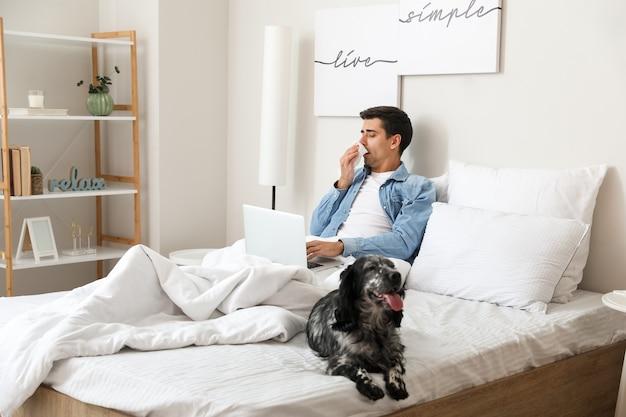 Chory człowiek z psem pracuje na laptopie w domu