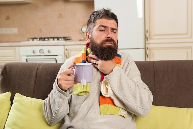 Chory człowiek zostaje w domu. młody człowiek sprawdza jego objawy. mężczyzna trzyma kubek z gorącą herbatą. samoizolacja. kwarantanna koronawirusa.