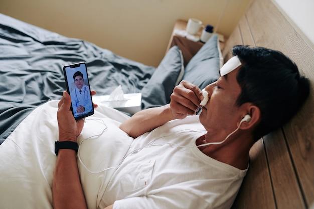 Chory dojrzały azjata wydmuchuje nos, gdy wideo dzwoni do swojego lekarza