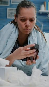 Chory dorosły czyta etykietę butelki z pigułkami i tabletką kapsułek
