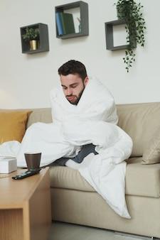 Chory facet zawinięty w koc siedzi na kanapie przed stołem z lekarstwami w salonie podczas przebywania w domu z powodu koronawirusa
