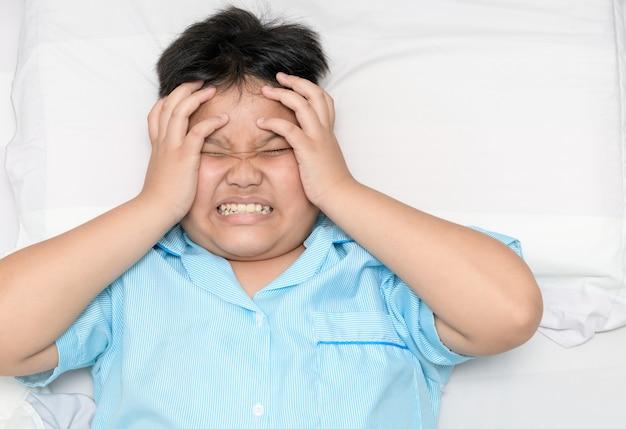 Chory gruby chłopiec cierpi na ból głowy na łóżku,