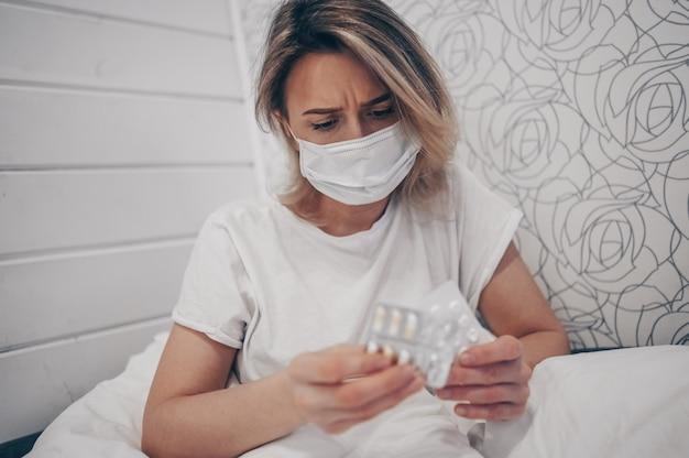 Chory kobietę leżącą w łóżku trzymając pigułki w domu kwarantanny izolacji. koncepcja covid-19 wirusa koronowego. zakażenie powoduje pierwszy objaw choroby układu oddechowego