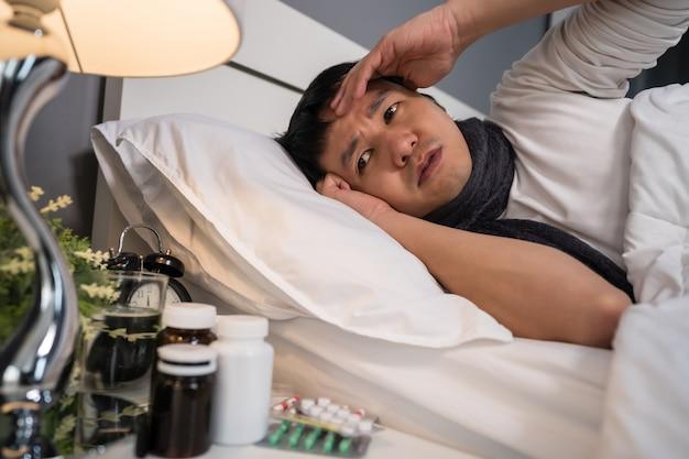 Chory ma ból głowy w łóżku