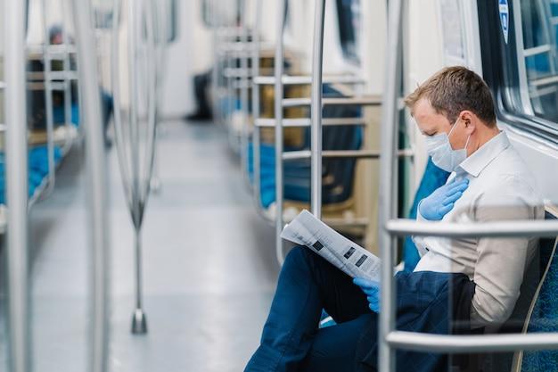 Chory ma problemy z oddychaniem, trzyma rękę na klatce piersiowej, podróżuje metrem, nosi maskę medyczną i gumowe rękawiczki. koronawirus pandemia. silny spadek ruchu pasażerskiego z powodu kwarantanny