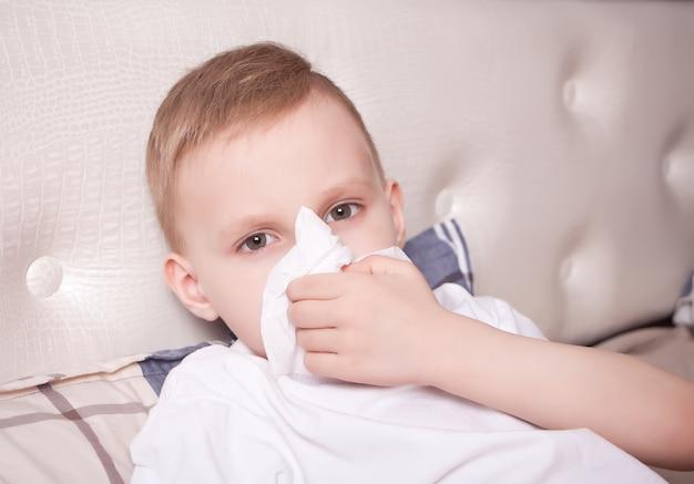 Chory mały blond chłopiec wieje jej nos