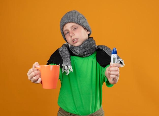 Chory mały chłopiec ubrany w zieloną koszulkę w ciepłym szaliku i czapce pokazujący filiżankę gorącej herbaty i termometr źle się czuje chory i nieszczęśliwy stojąc nad pomarańczową ścianą