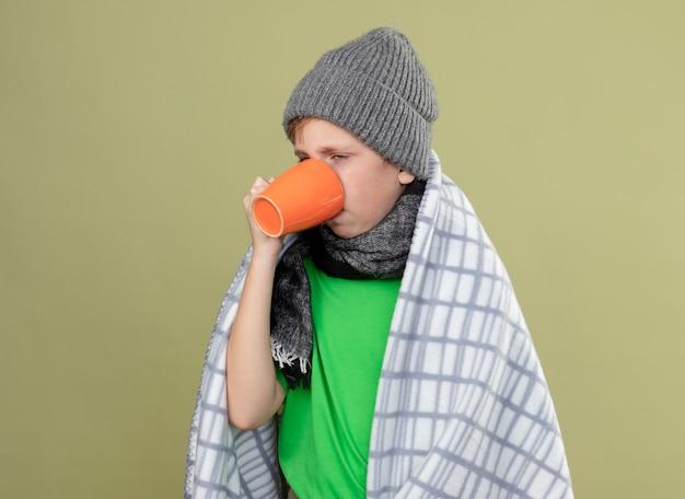 Chory mały chłopiec ubrany w zieloną koszulkę w ciepłym szaliku i czapce zawinięty w koc pijący gorącą herbatę cierpiący na zimno stojący nad jasną ścianą