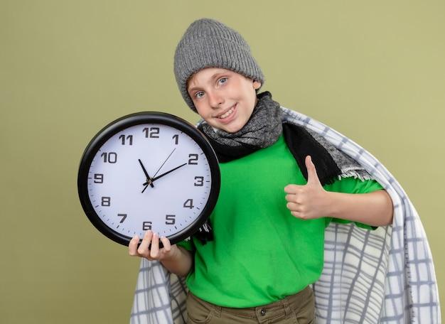 Chory mały chłopiec ubrany w zieloną koszulkę w ciepłym szaliku i czapce zawinięty w koc trzyma zegar ścienny uśmiechnięty pokazując kciuki do góry czuje się lepiej stojąc nad jasną ścianą