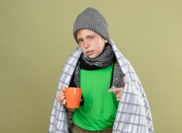 Chory mały chłopiec ubrany w zieloną koszulkę w ciepłym szaliku i czapce zawinięty w koc trzymający kubek gorącej herbaty wskazujący palcem na niego stojąc nad jasną ścianą