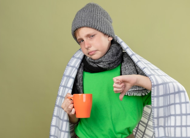 Chory mały chłopiec ubrany w zieloną koszulkę w ciepłym szaliku i czapce zawinięty w koc trzymający kubek gorącej herbaty z kciukami w dół stojąc nad jasną ścianą