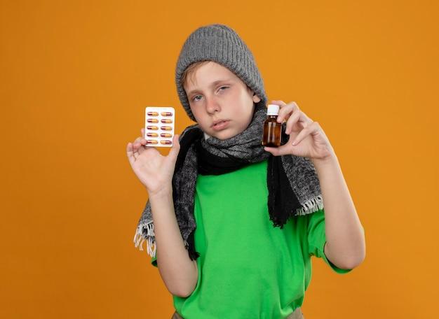 Chory mały chłopiec ubrany w zieloną koszulkę w ciepłym szaliku i czapce źle się czuje, pokazuje butelkę z lekarstwami i pigułki nieszczęśliwy i chory stojąc nad pomarańczową ścianą