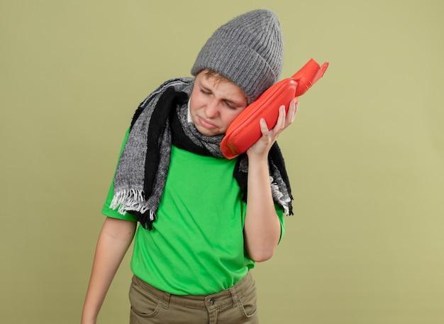Chory mały chłopiec ubrany w zieloną koszulkę w ciepłym szaliku i czapce źle się czuje trzymając butelkę z wodą, aby utrzymać ciepło, opierając na niej głowę chory i nieszczęśliwy, stojąc nad jasną ścianą