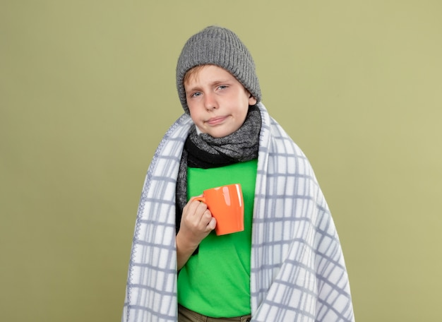 Chory mały chłopiec ubrany w zieloną koszulkę w ciepłym szaliku i czapkę zawinięty w koc trzymający kubek gorącej herbaty wygląda na nieszczęśliwego i chorego stojącego nad jasną ścianą