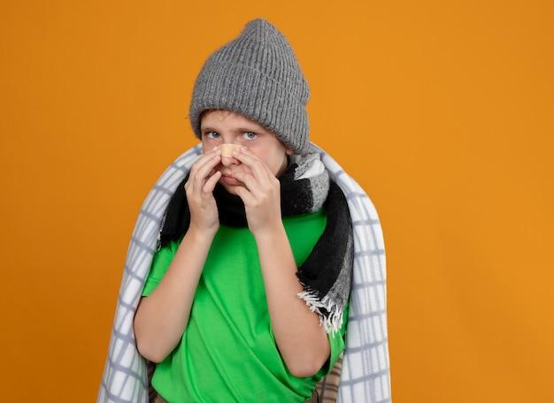 Chory mały chłopiec w ciepłej czapce i szaliku zawinięty w koc, zakładający łatę na nos, nieszczęśliwy i chory, stojący nad pomarańczową ścianą