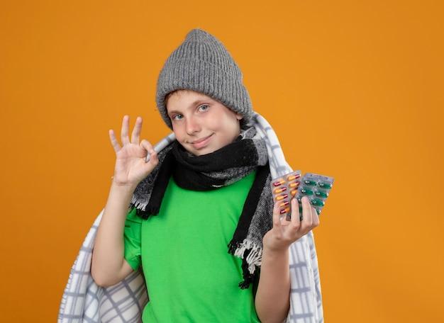 Chory mały chłopiec w ciepłej czapce i szaliku zawinięty w koce, pokazując pigułki, czuje się lepiej, uśmiecha się