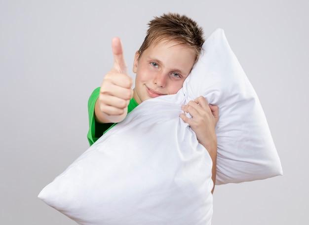 Chory mały chłopiec w zielonej koszulce czuje się lepiej przytulając poduszkę patrząc pokazując kciuki do góry uśmiechnięty stojący nad białą ścianą