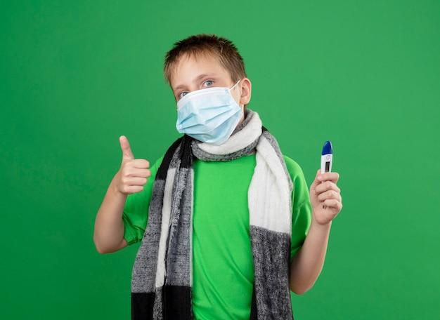 Chory mały chłopiec w zielonej koszulce i ciepłym szaliku wokół szyi, noszący maskę ochronną na twarz, trzymający thremometr, wyglądający lepiej, pokazujący kciuki do góry stojąc nad zieloną ścianą