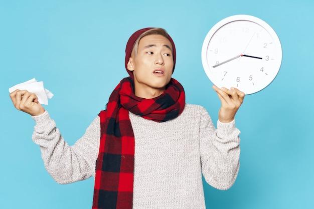 Chory mężczyzna azji, trzymając zegar