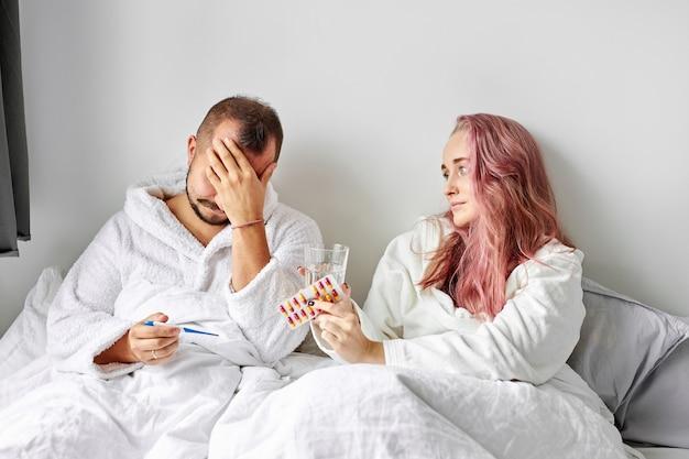 Chory mężczyzna ma gorączkę i ból głowy leżąc na łóżku, kobieta go podtrzymuje, podaje leki