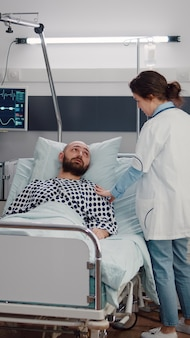 Chory mężczyzna odpoczywa w łóżku, podczas gdy lekarz terapeuta monitoruje regenerację oddechową pracując na oddziale szpitalnym