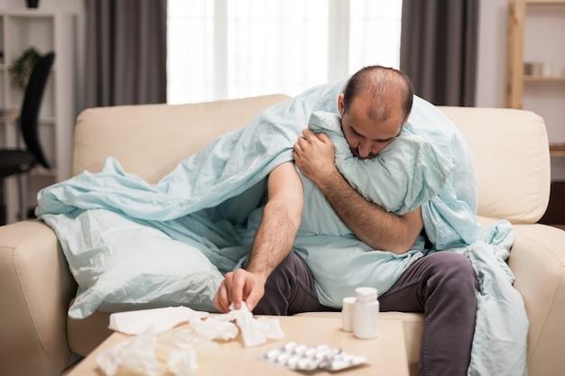 Chory mężczyzna owinięty w koc sięgający po serwetki podczas samoizolacji.