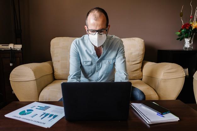 Chory mężczyzna pracuje odizolowywam z twarzy maską od domu