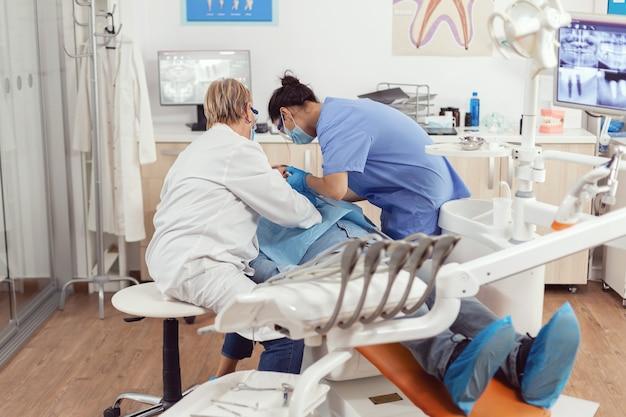 Chory mężczyzna siedzący na fotelu dentystycznym podczas badania lekarskiego