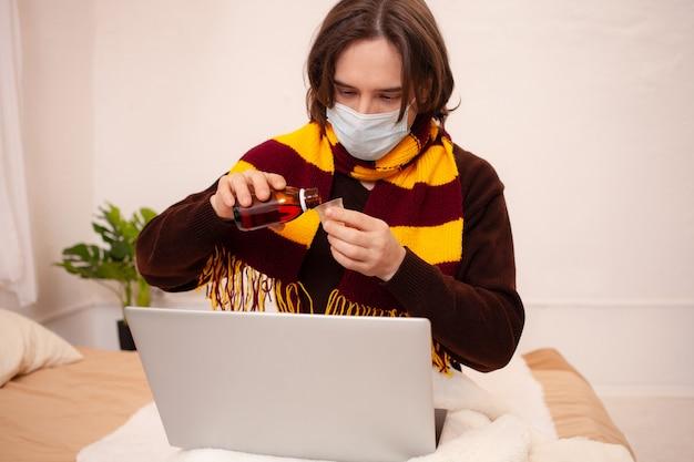 Chory mężczyzna siedzi przy laptopie w masce i szaliku. koronawirus, covid, kwarantanna domowa. człowiek nalewa sobie lekarstwa, leczy grypę, przeziębienie