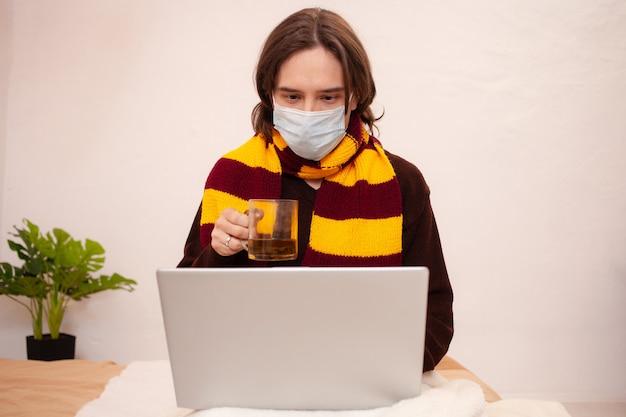 Chory mężczyzna siedzi przy laptopie w masce i szaliku. koronawirus, covid, kwarantanna domowa. mężczyzna pije herbatę z przeziębienia.