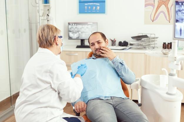 Chory mężczyzna skarży się na ból zęba, rozmawiając ze starszą kobietą stomatologem o leczeniu stomatologicznym
