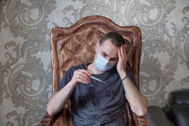 Chory mężczyzna sprawdza jego temperaturę z termometrem w domu. kwarantanna. covid-19