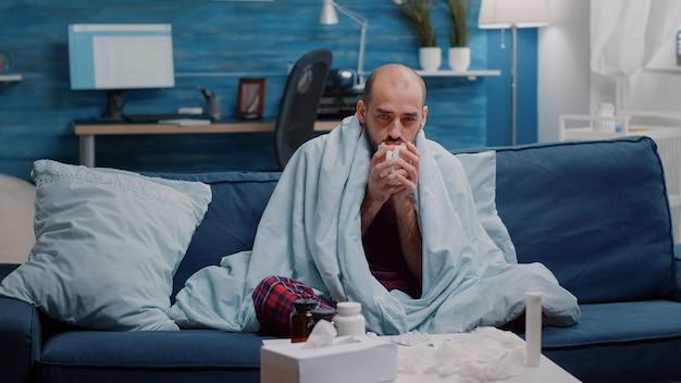 Chory mężczyzna trzymający filiżankę herbaty, aby leczyć przeziębienie i grypę