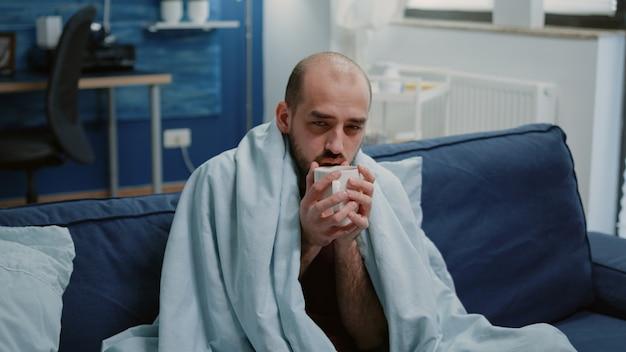 Chory mężczyzna trzymający filiżankę herbaty i patrzący w kamerę