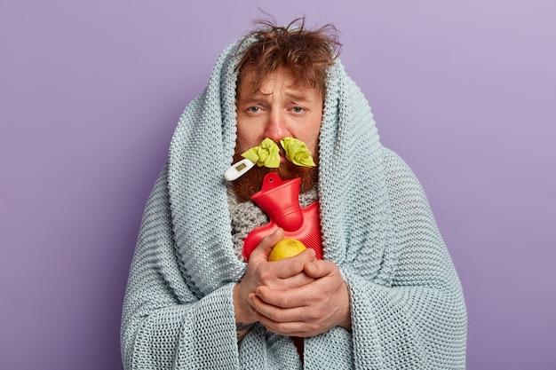 Chory mężczyzna w ciepłej odzieży z termometrem i workiem na wodę