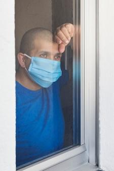 Chory mężczyzna w masce chirurgicznej zostaje poddany kwarantannie w domu i wygląda przez okno