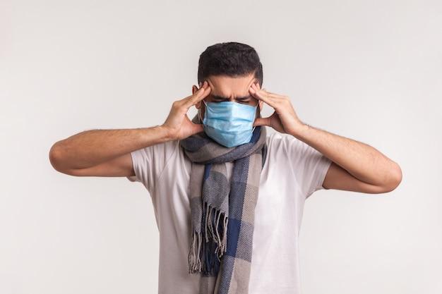 Chory mężczyzna w masce i szaliku cierpiący na ból głowy, pocierający bolesne skronie, mający objawy covid-19
