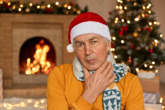 Chory mężczyzna w pomarańczowym swetrze, szaliku i świątecznej czapce cierpi na ból gardła