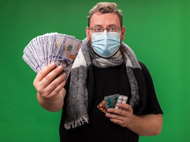 Chory mężczyzna w średnim wieku noszący maskę medyczną i szalik na zielonej ścianie