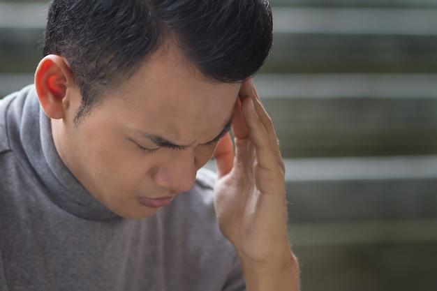 Chory mężczyzna z azji południowo-wschodniej z bólem głowy, depresją, stresem