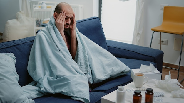 Chory mężczyzna z bólem głowy, tarcie skroni i mdłości