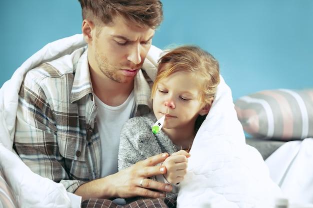Chory mężczyzna z córką w domu. leczenie w domu. walka z chorobą. opieka medyczna. wola rodzinna. zima, grypa, zdrowie, ból, rodzicielstwo, koncepcja relacji. relaks w domu